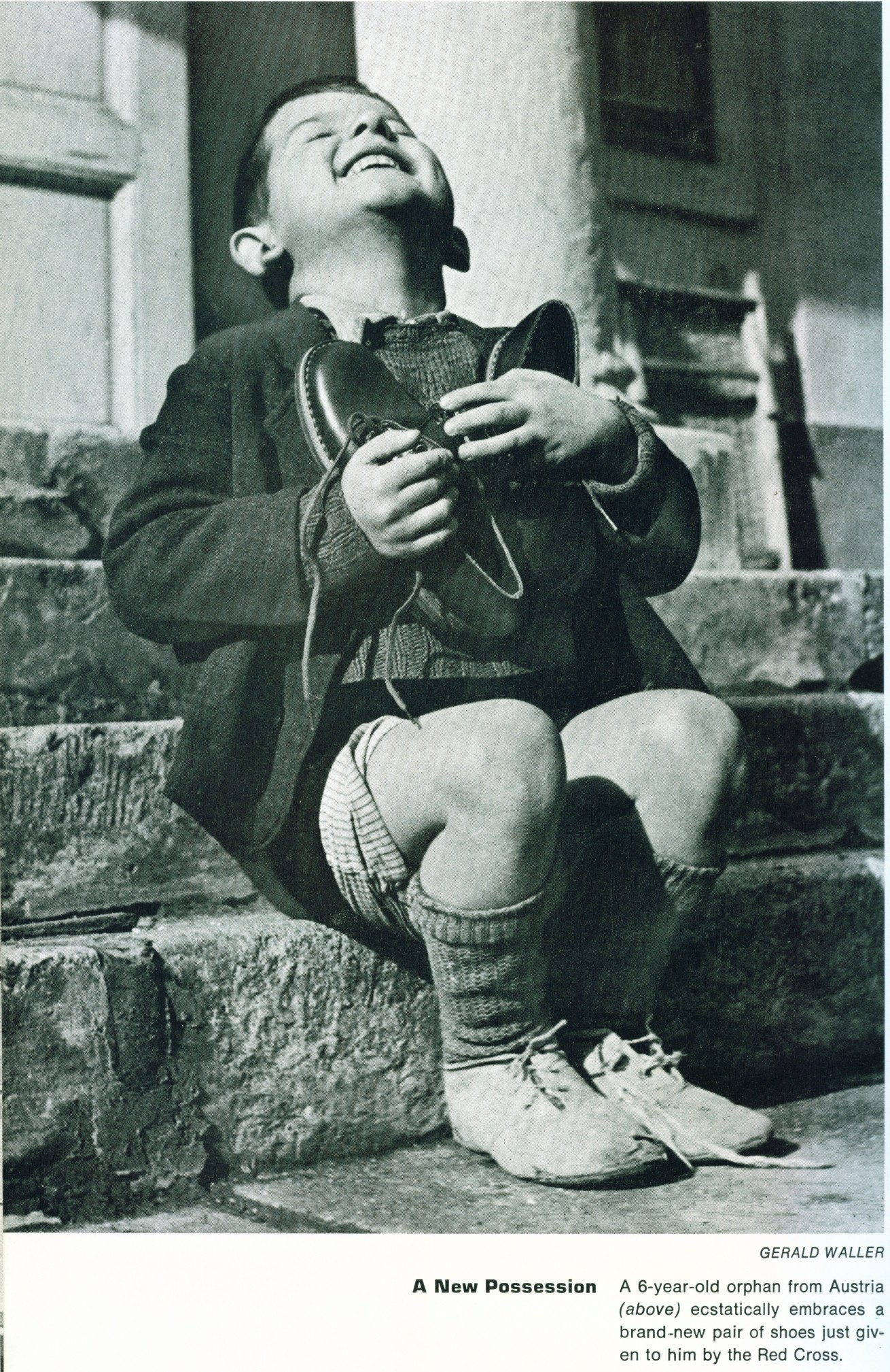 A 6 year old orphan from Austria ecstatically embraces a brand new pair of shoes given to him by the red cross
